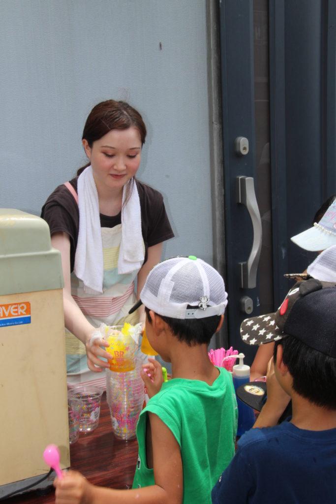 子どもたちにかき氷を手渡す小林タバサさん(注)中日新聞8月9日静岡版掲載